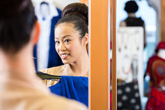 Asian Woman trying clothes in shop mirror Royalty Free Stock Images