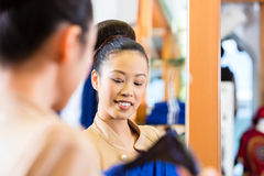 Asian Woman trying clothes in shop mirror Royalty Free Stock Photos