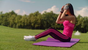 Asian woman tying laces on her sneakers. Fit girl warming up before training stock footage