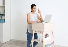 Asian woman typing on laptop at stand-up workplace stock photos