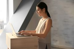 Free Asian Woman Typing On Laptop At Stand-up Workplace Stock Image - 105132511