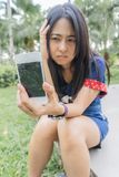 Asian woman unhappily at broken smart phone. Asia girl show broken mobilephone and she very sad royalty free stock images