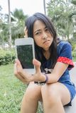 Asian woman unhappily at broken smart phone. Asia girl show broken mobilephone and she very sad Stock Images