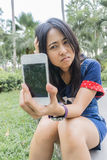 Asian woman unhappily at broken smart phone. Royalty Free Stock Photography