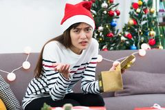Asian woman upset when open gold xmas gift box at holiday party Royalty Free Stock Images