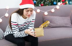 Asian woman upset when open gold xmas gift box at holiday party. On sofa,boredom Christmas party present Stock Images