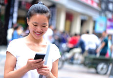 Asian woman use cellphone at shopping street Royalty Free Stock Images