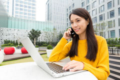 Asian woman use computer and talk to cellphone Royalty Free Stock Images
