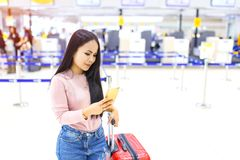 Asian woman use of mobile phone in front of counter check in airline at international airport Stock Images