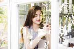 Asian women use smartphone in cafe shop. Royalty Free Stock Images