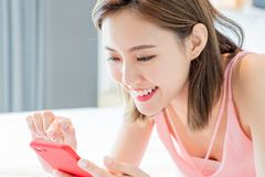 Asian woman use smartphone happily. On the bed at home stock image