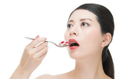 Asian woman use spoon taking numerous of medicine pill Stock Image