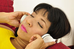 Asian woman uses bluetooth stereo headphones Royalty Free Stock Images