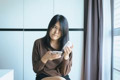 Asian woman using cell phone searching information and reading medicine label and prescription medications,Health care and people. Concept royalty free stock images