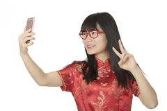Asian woman using a cell phone to take a selfie isolated on whit Stock Photo
