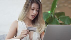 Asian woman using computer for online purchase with credit card stock video
