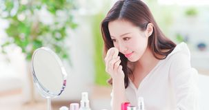Asian woman using cosmetic sponge stock photo