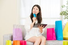 Asian woman using credit card online shopping with pad. Attractive asian woman using credit card paying online shopping with pad sitting on sofa colorful Royalty Free Stock Photography
