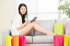 Asian woman using credit card online shopping with pad. Attractive asian woman using credit card paying online shopping with pad sitting on sofa colorful Stock Photo