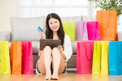 Asian woman using credit card online shopping with pad. Attractive asian woman using credit card paying online shopping with pad sitting on sofa colorful Royalty Free Stock Image