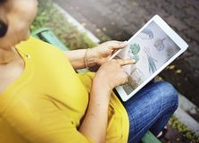 Asian woman is using digital tablet at the park Stock Photo