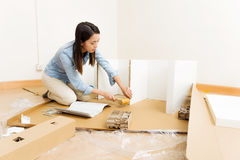 Asian woman using hammer for assembling furniture Stock Photo