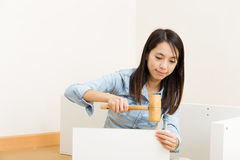 Asian woman using hammer for closet assembling Royalty Free Stock Photos