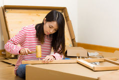 Asian woman using hammer for furniture assembling Stock Photography