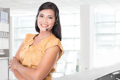 Asian woman using a headset, smiling at the camera Royalty Free Stock Photography