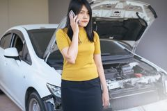 Asian woman using mobilephone with broken down car. Asian woman using her mobilephone with broken down car Royalty Free Stock Images
