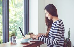 Asian woman using on laptop computer near window at cafe restaurant,Digital age lifestyle,Technolgy using concept. Asian woman using on laptop computer near royalty free stock photos