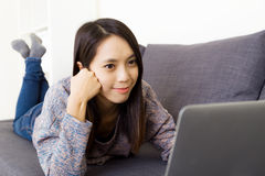 Asian woman using laptop on couch Stock Photography