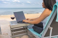 Asian woman using laptop with glass of red wine on table royalty free stock photos