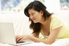 Asian woman using laptop at home Royalty Free Stock Photos