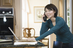 Asian woman using laptop in kitchen Stock Photo