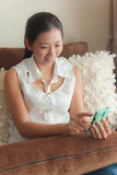An Asian woman using mobile device Royalty Free Stock Photos