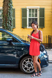 Asian woman using mobile phone app for car sharing. Service or city traffic information in front of her house. New car owner using phone to check status stock images