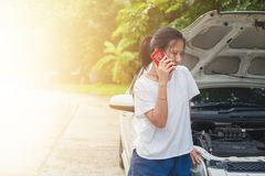 Asian woman using mobile phone and calling for help while the ca Royalty Free Stock Image