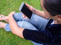 Woman using mobile phone in the lawn. stock images