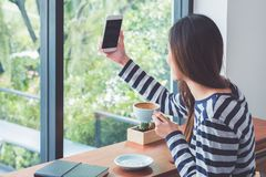 Asian woman using on mobile phone live on social media while dri. Nking coffee near window at cafe restaurant,Digital age lifestyle,Technolgy using concept Stock Photo