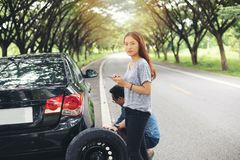 Asian woman using mobile phone while looking and Stressed man sitting after a car breakdown on street stock photos