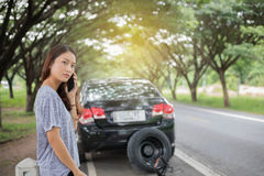 Asian woman using mobile phone while looking and Stressed woman. After  broken down car on street Stock Photography
