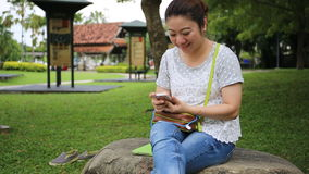 Asian woman using mobile phone in the park . stock footage
