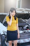 Asian woman using mobilephone with broken down car. Asian woman using her mobilephone with broken down car Stock Photography