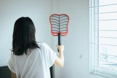 Asian woman using mosquito swatter at home,Female with mosquito electric net racket in bedroom stock image