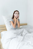 Asian woman using the paper mask and sitting on bed Royalty Free Stock Image