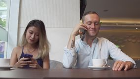 Asian woman using phone and caucasian man speaking smartphone. Asian woman using phone and caucasian man speaking smartphone during lunch time stock footage