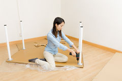 Asian woman using screwdriver for assembling furniture Stock Images