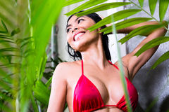 Asian woman using shower in tropical garden Royalty Free Stock Photo