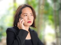 Asian woman using smart phone with blur green garden background. royalty free stock photo